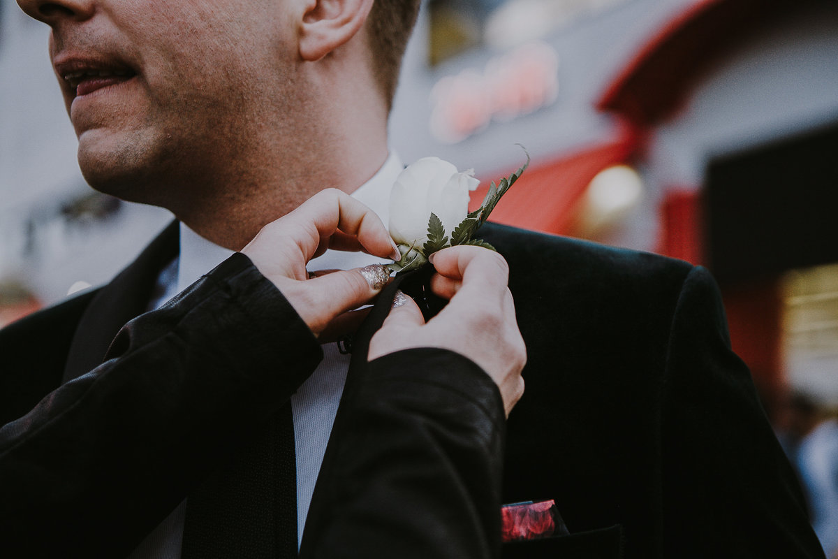 Lake Tahoe elopement pictures bride adjusts groom's boutonniere