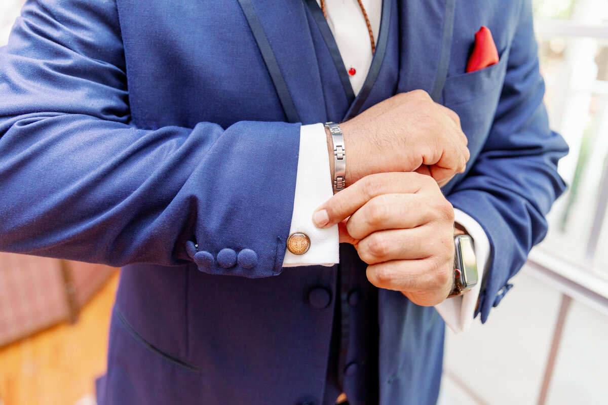 Groom Adjusting His Sleeves in His Wedding Day Suit