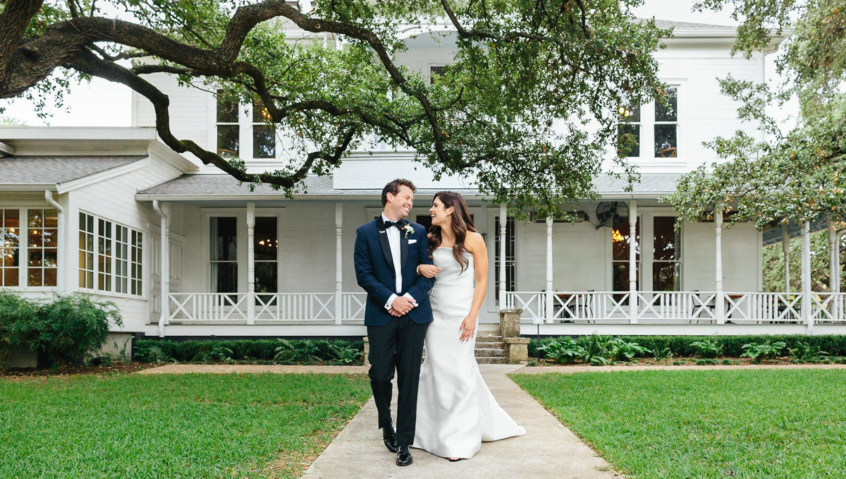 Bride and Groom walking in front of white southern mansion Matties Wedding Austin