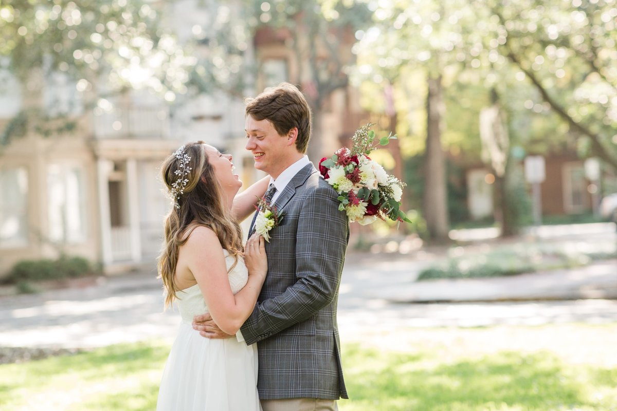bride and groom laughing at a square in savannah after their elopement
