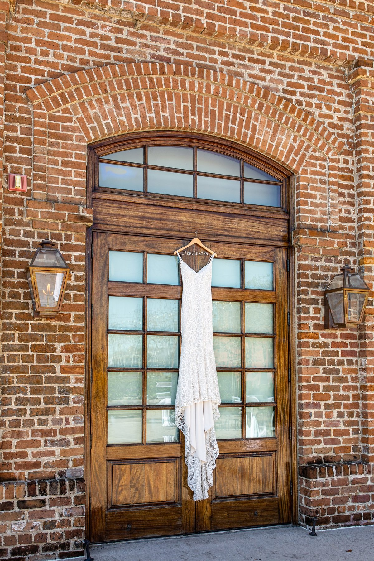 wedding dress hanging on the door of the charles morris center in savannah