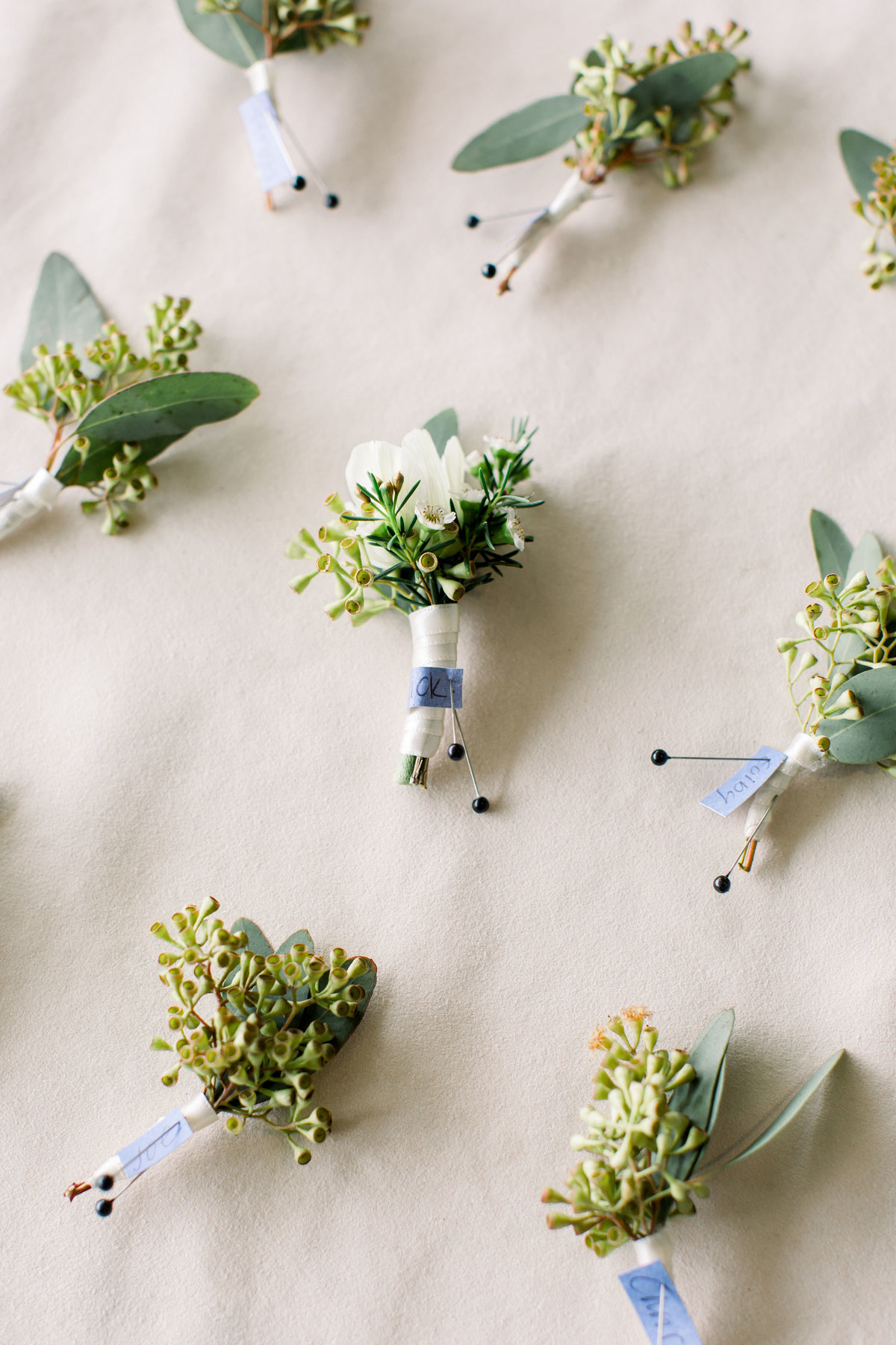 Groom and groomsmen boutonnieres pinned to board at Woodlands wedding in Colorado