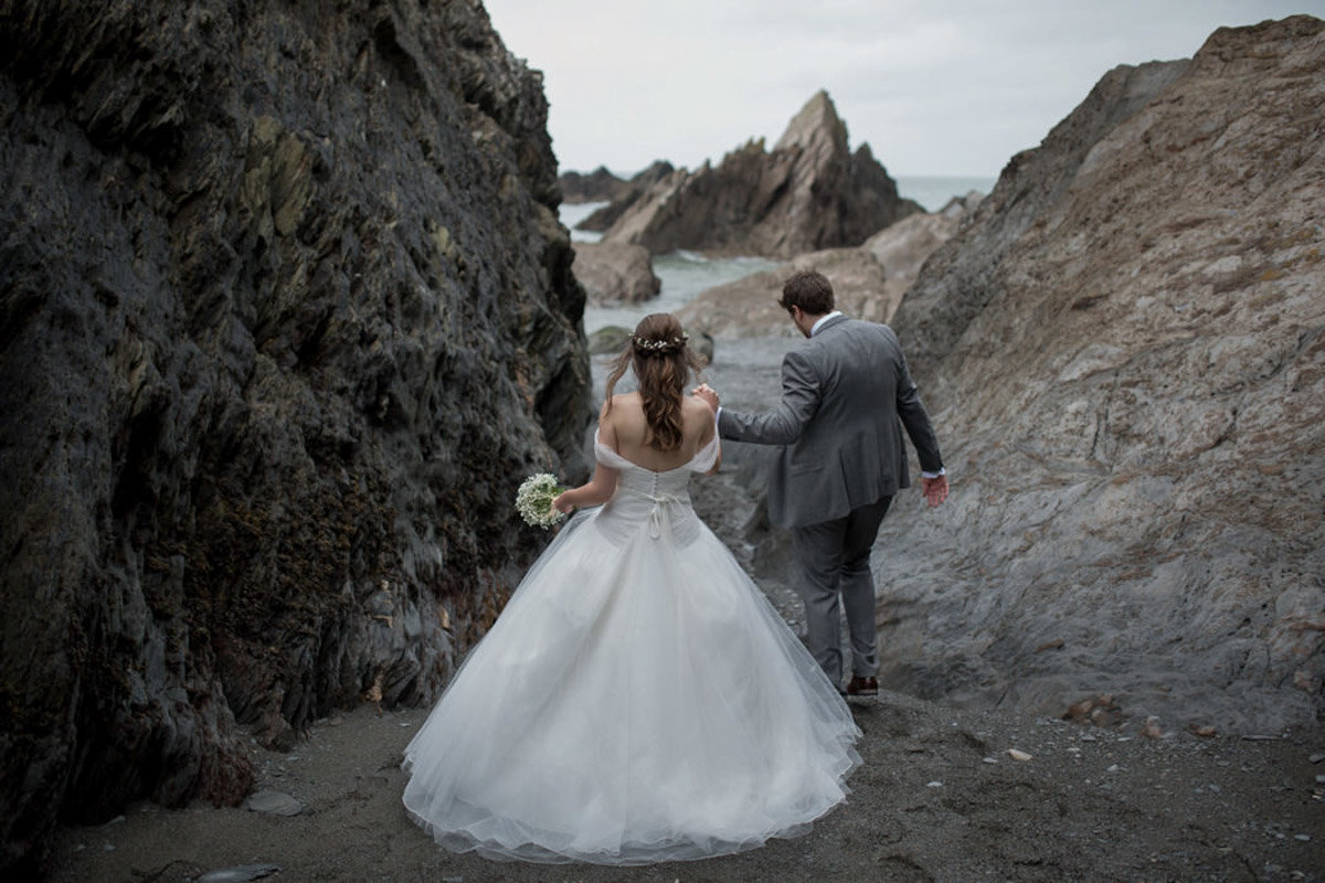 Groom helping his Bride through the rocks at Tunnels Beaches