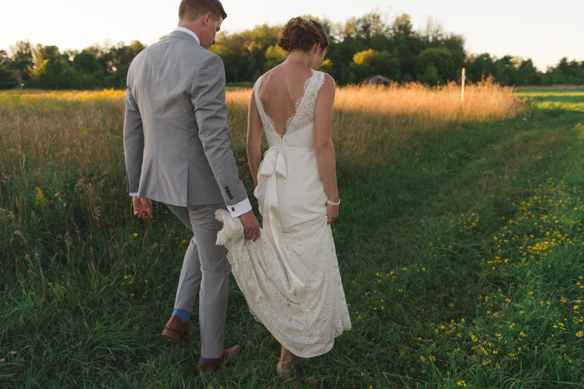 Groom holding bride's train as they walk in the fields of Strathmere at sunset in Ottawa