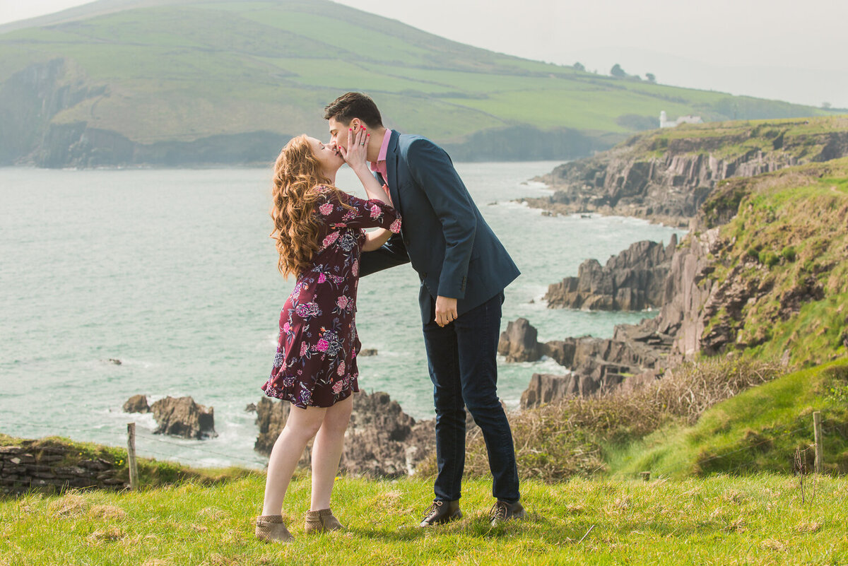 Young couple with red hair kissing in a field overlooking the sea