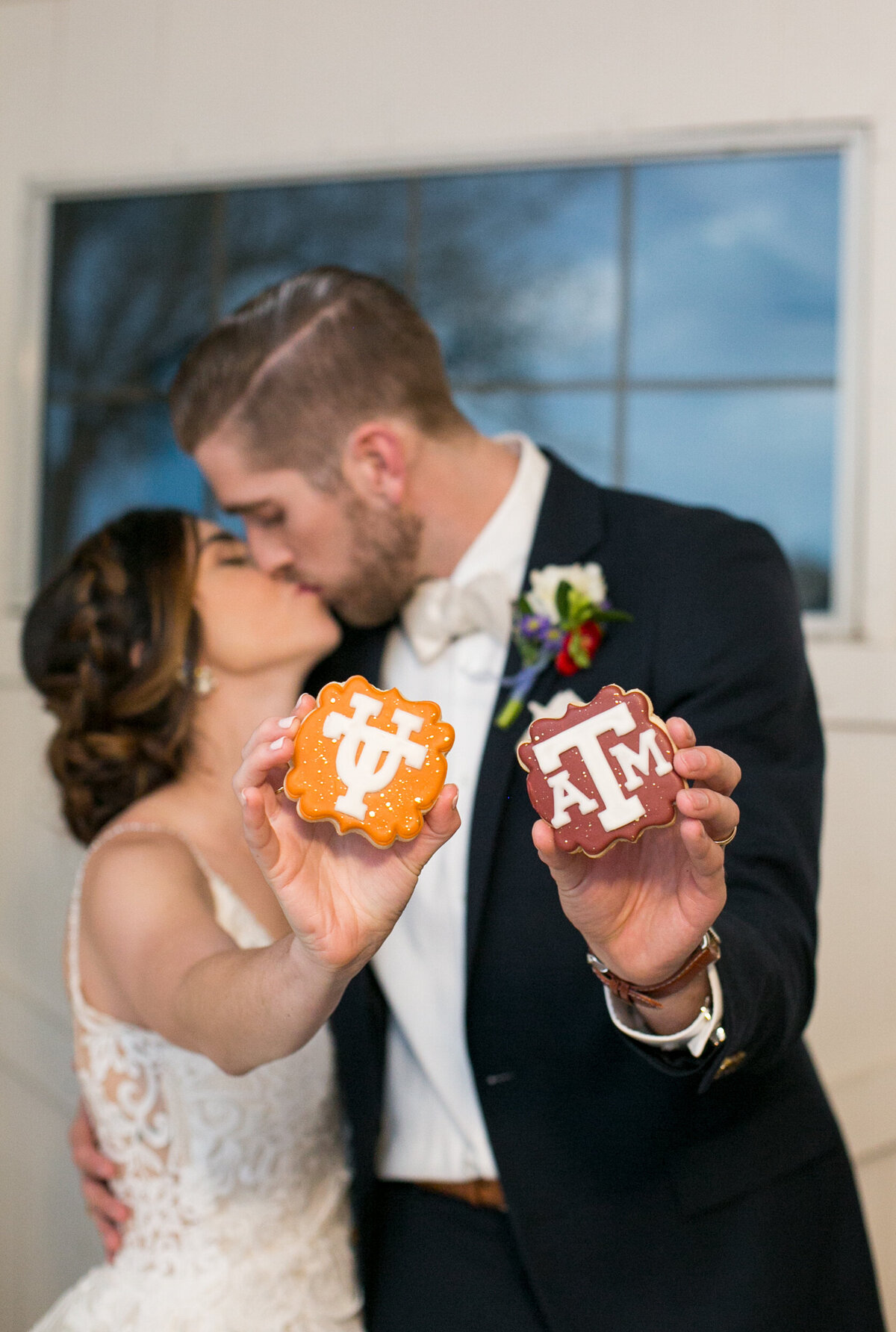 A bride and groom kissing on wedding day. Holding cookies from A&M and UT