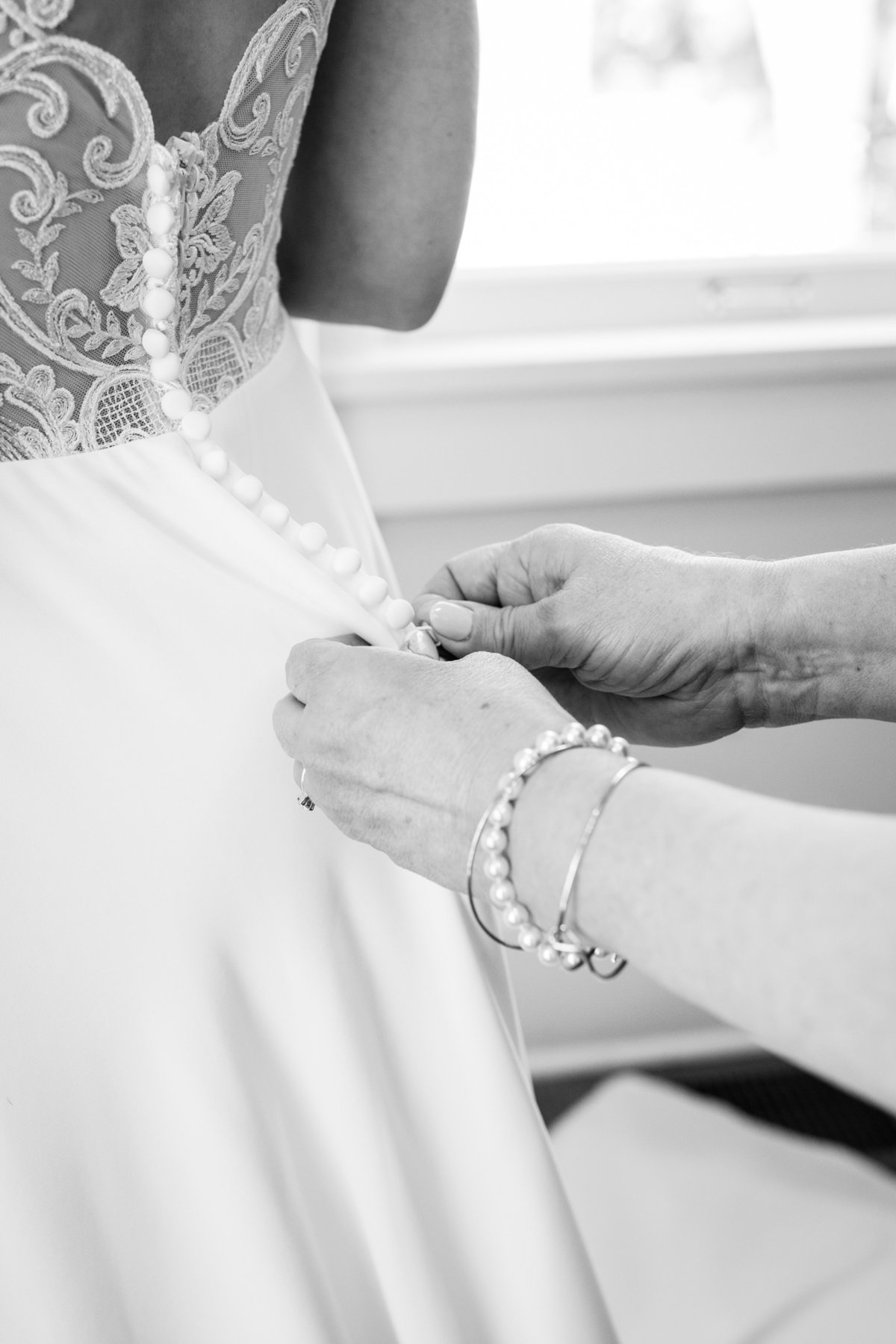 close up photo of mom buttoning dress of bride daughter