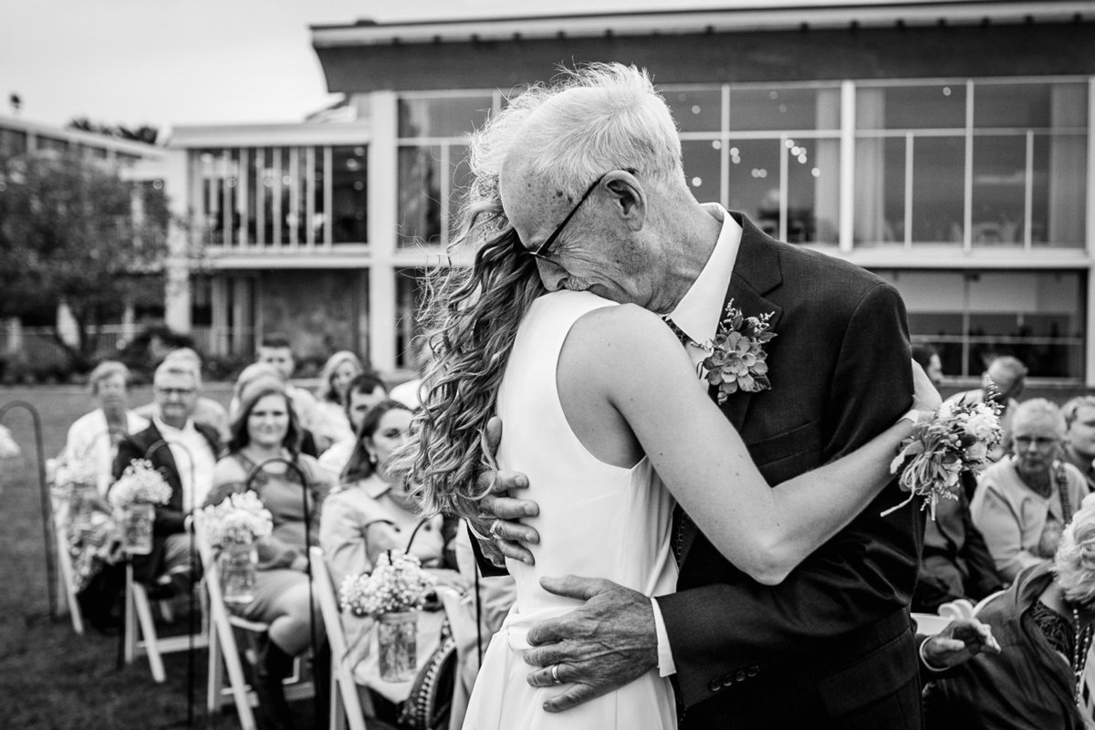 The father-of-the-bride kisses his daughter during an Illinois Beach Resort wedding ceremony.