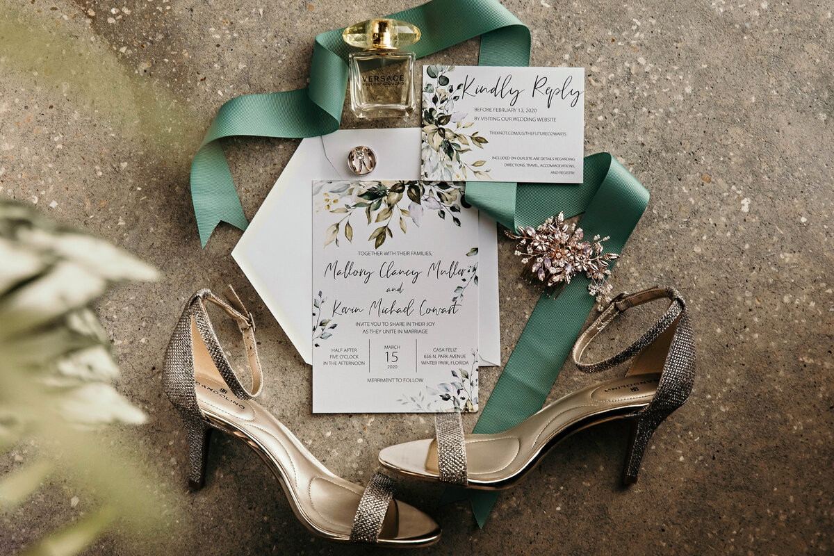 An image of the bride's silver heels and beautiful hair decoration, her perfume bottle and the wedding rings, all artistically surrounding the wedding invitation by Garry & Stacy Photography Co - Tampa wedding photographers