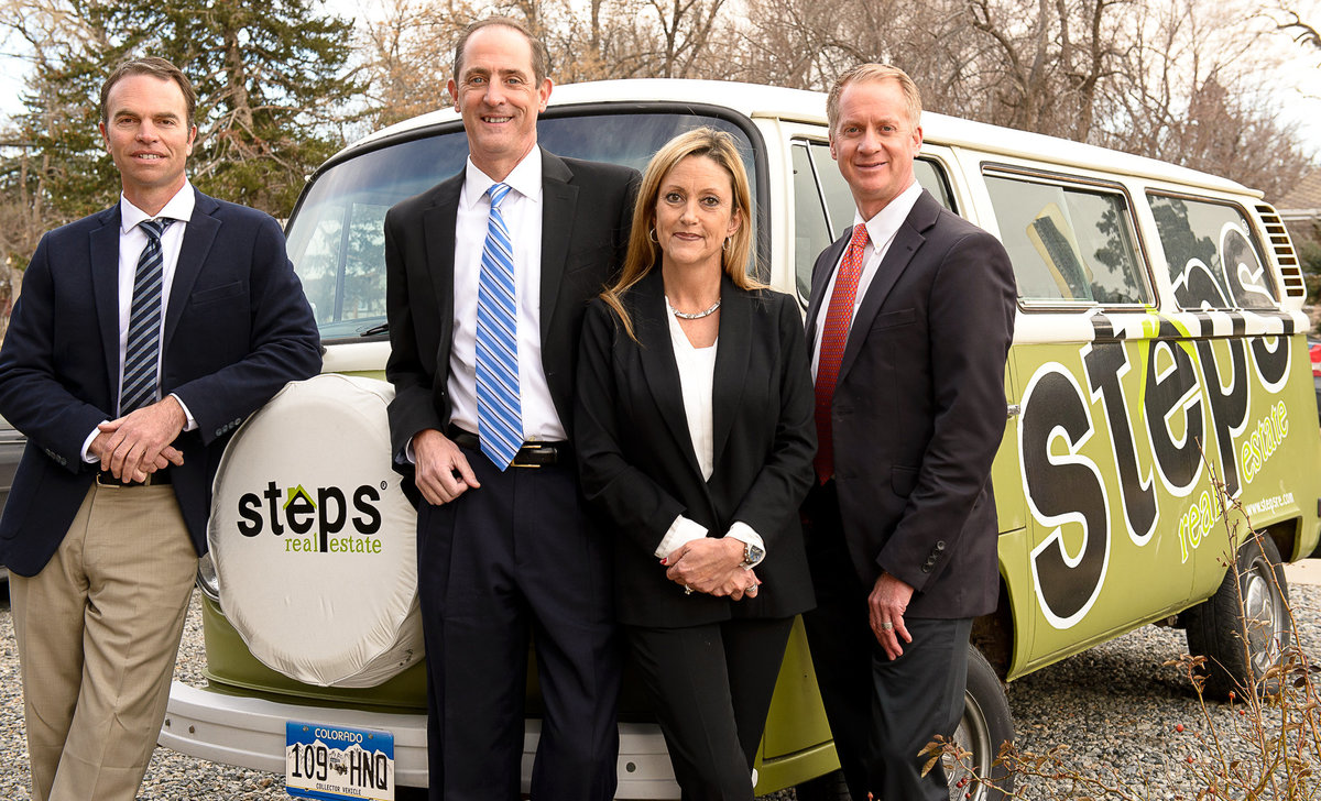 Real estate team poses for branding photography session in front of green VW van