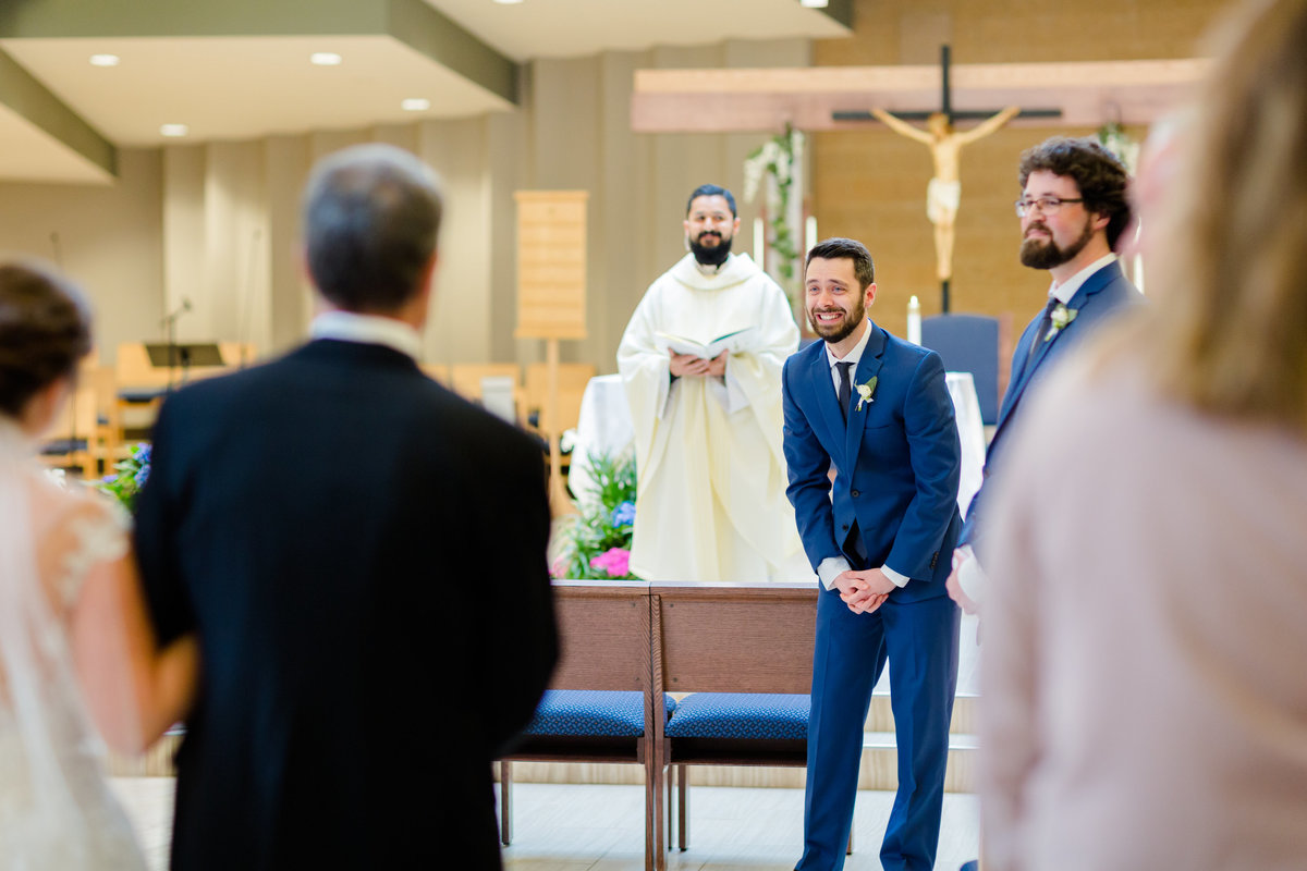 Groom sees his bride for the first time walking down the aisle - Catholic wedding in Milwaukee, Wisconsin