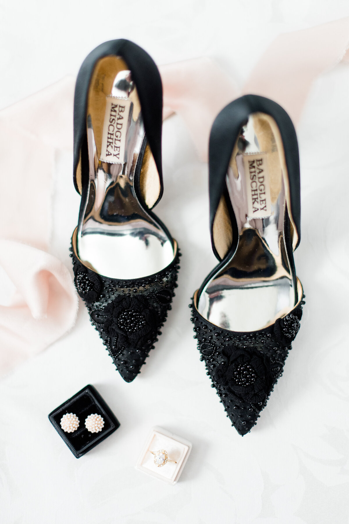 A pair of black pointed toe badgley mischka shoes with flower detail sit on a Kate Spade mat with earrings and rings in The Mrs. Boxes