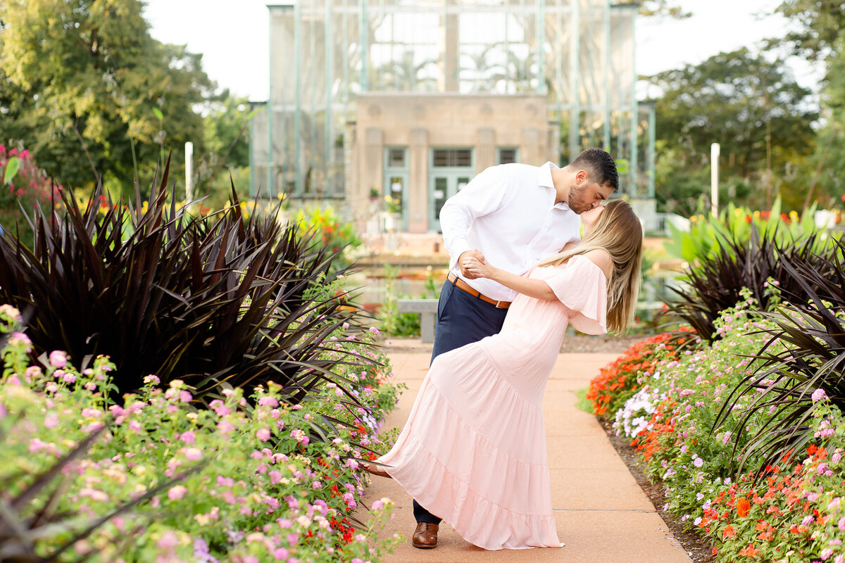 Summer Sunset Engagement Session with pink off the shoulder dress couple kissing by flowers at the Jewel Box in Forest Park in St. Louis by Amy Britton Photography Photographer in St. Louis