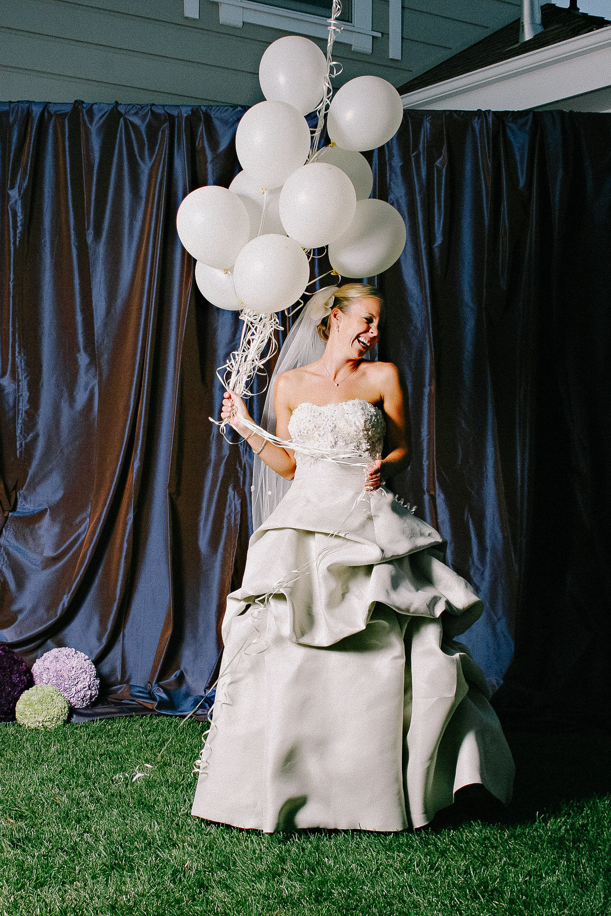 A bride poses with white balloons for her wedding in Napa.