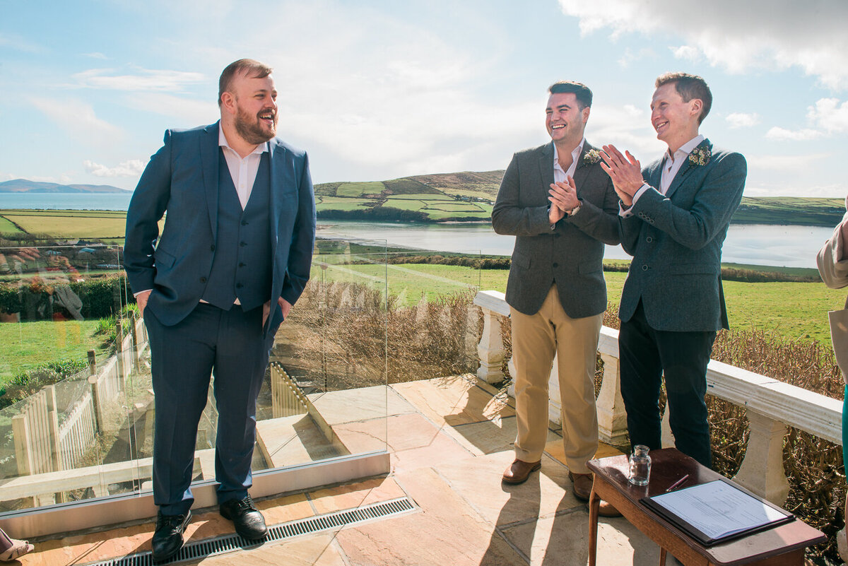 two grooms clapping on a sunny terrace laughing and looking at guest