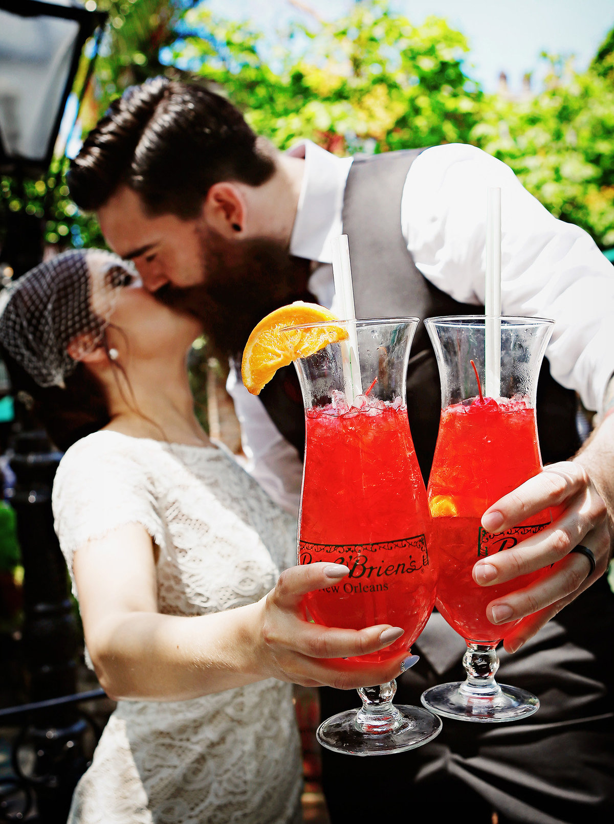NOLA bride and groom kiss in the background behind Pat O'Brien hurricane glasses