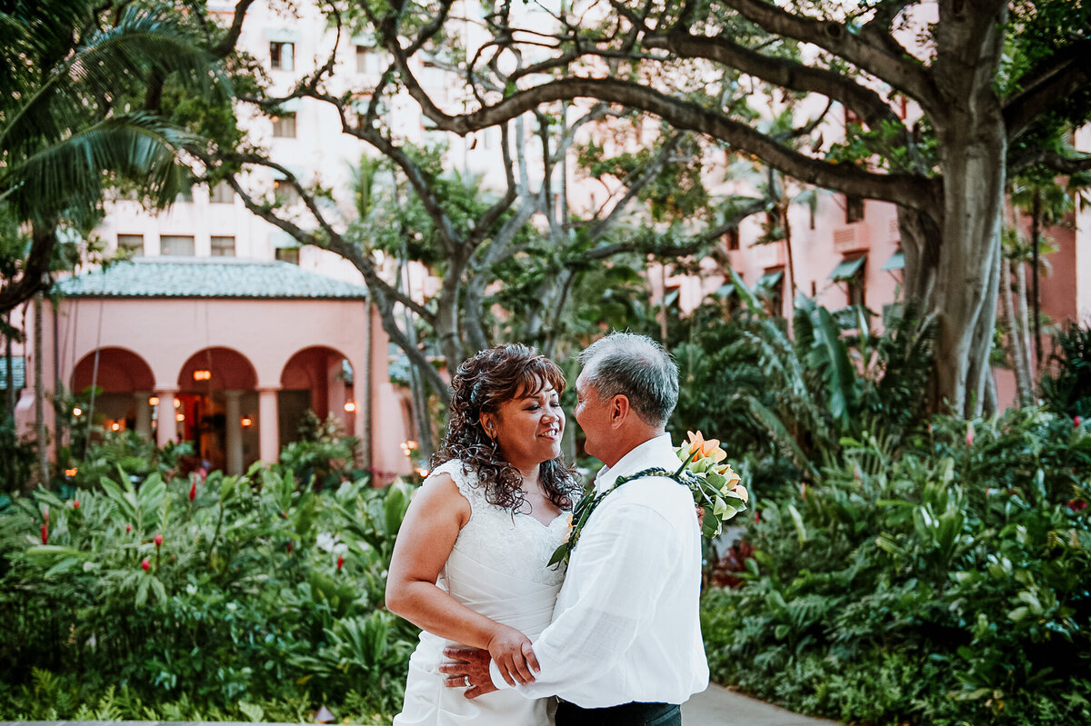 A Bride and Groom Pose for a Photo Outside of the Royal Hawaiian Hotel