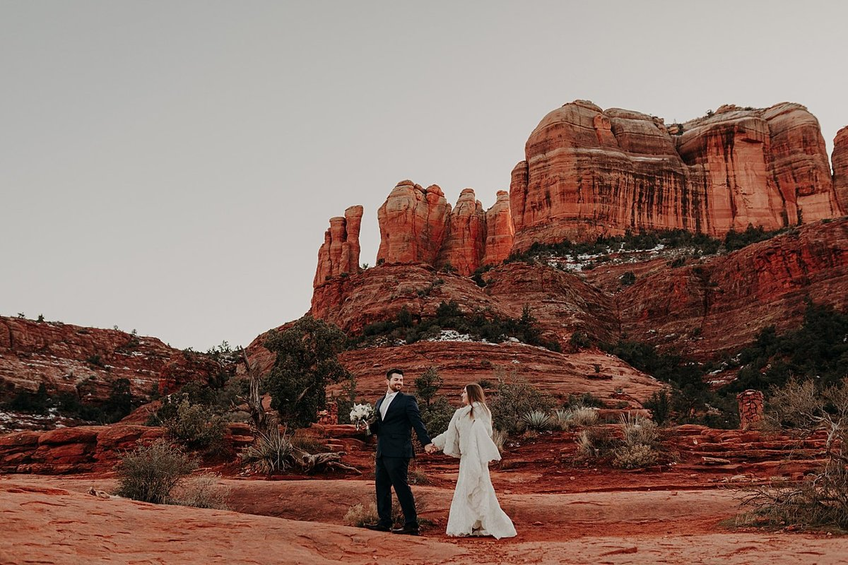 bride and groom walk across the orange red rocks at Cathedral Rock for wedding photos