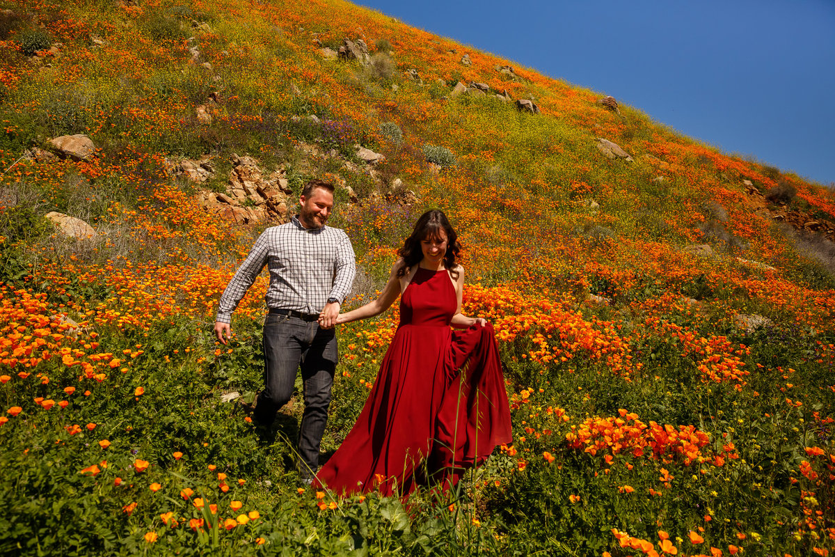 Couple running through California poppies on the trail