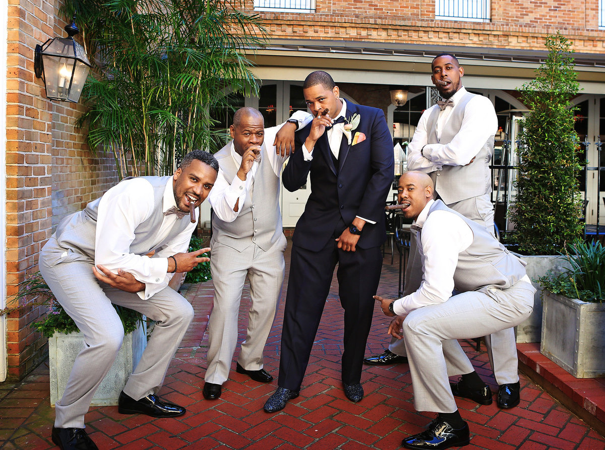 groom and groomsmen with cigars in the courtyard of the Chateau LeMoyne Hotel