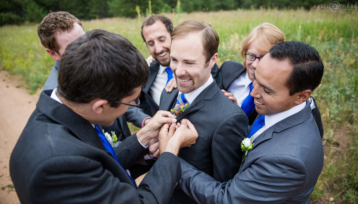 Groom surrounded by best friends gets help with his boutonniere at Wedgewood Mountain View Ranch in Colorado