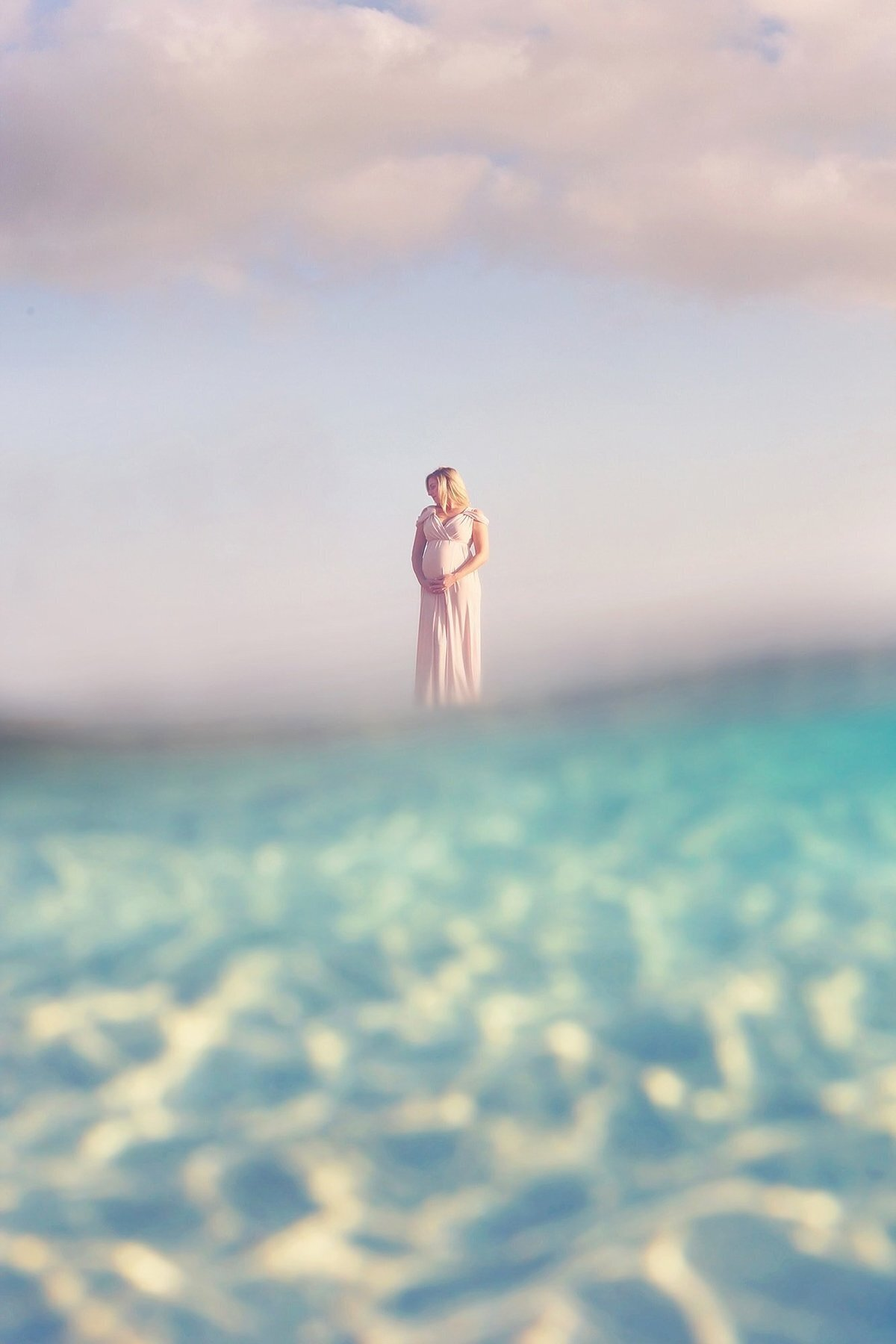 Pregnant woman in maternity gown standing in the water in Lahaina