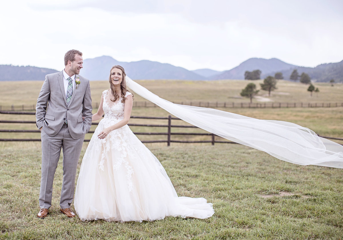 Bride and Groom in a field with mountains in Colorado wedding