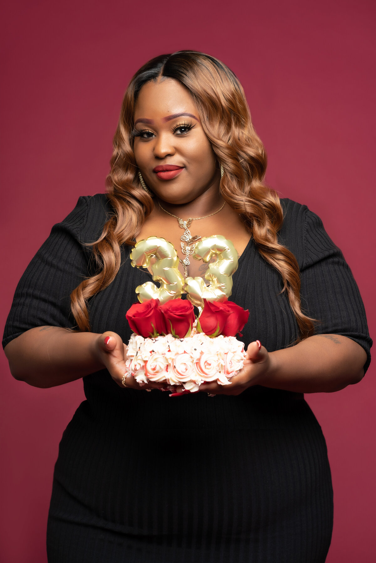 Black curvy woman in black dress with birthday cake
