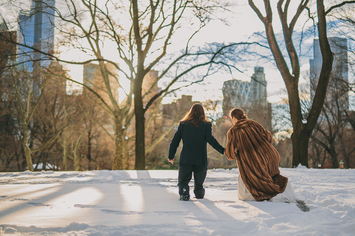 Bride & Groom trek through the snow in Central Park after their Central Park wedding in Manhattan, Ca.