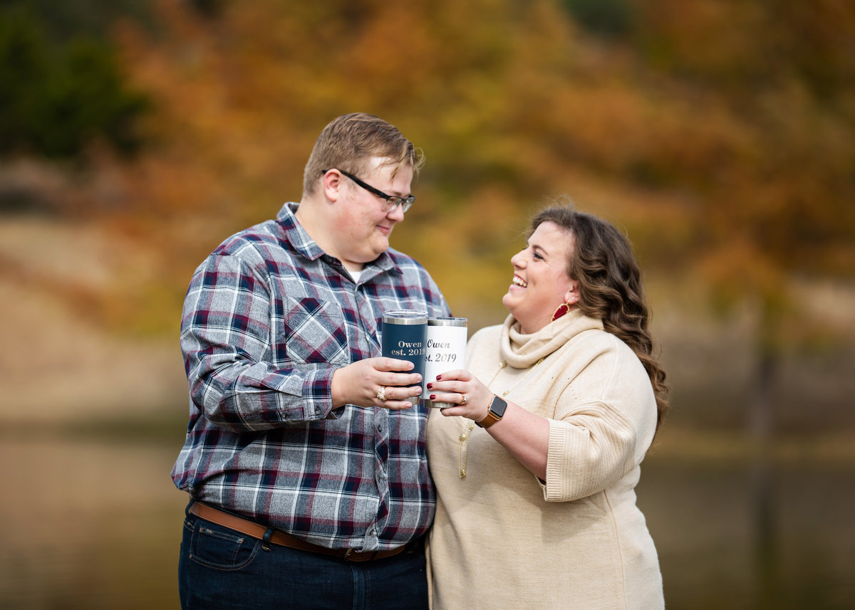 couple cheering with their Yeti fall by the lake