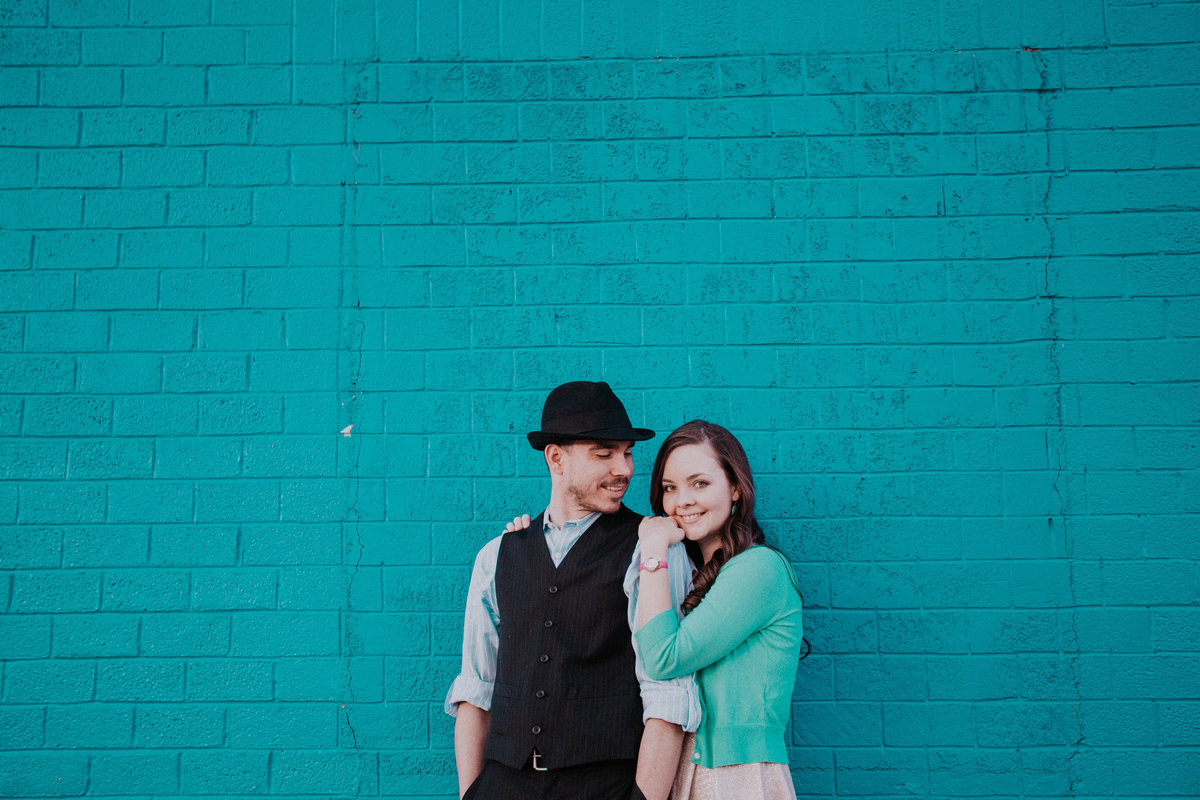 Lake Tahoe engagement pictures couple hugs in front of teal wall