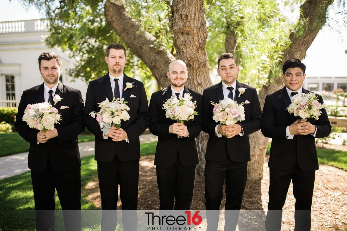 Fun photo of Groomsmen posing holding the Bridesmaid's bouquets