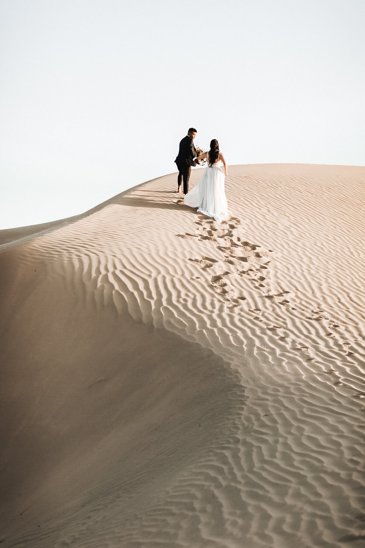 Couple wearing wedding attire climbing a sand dune.