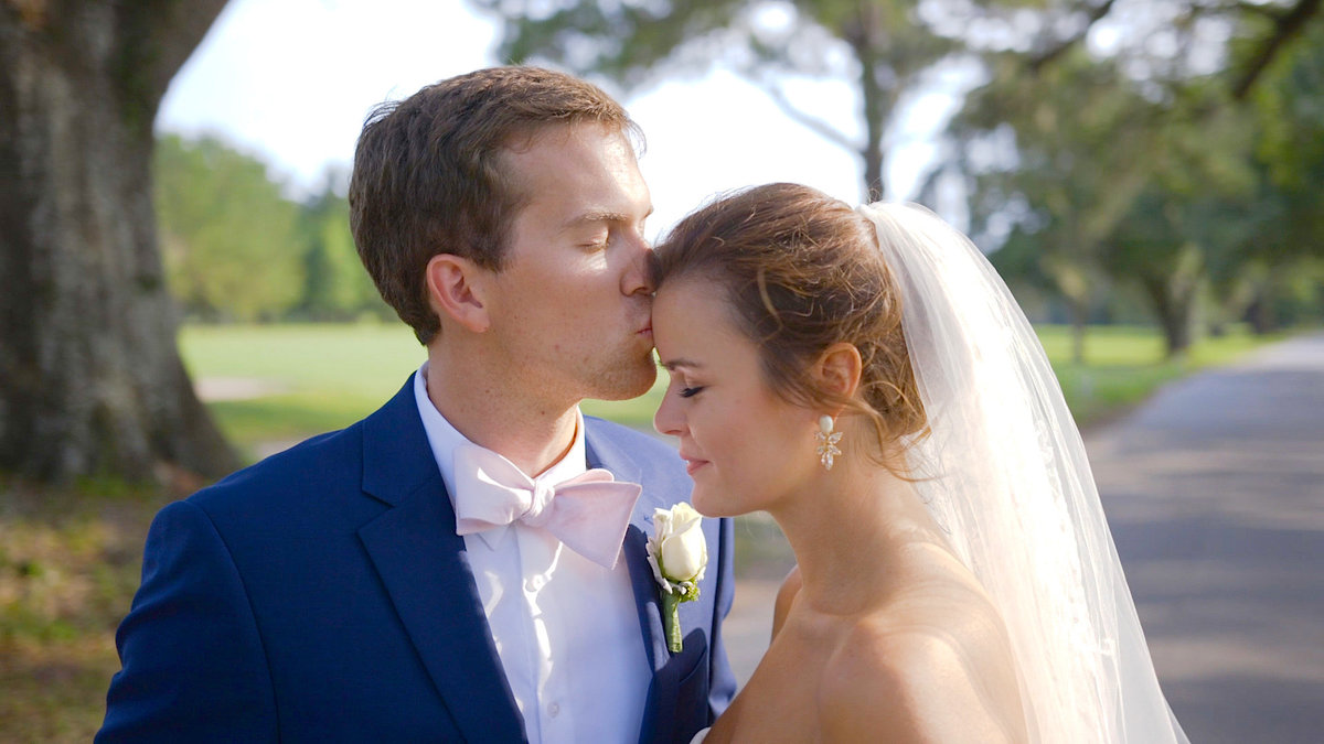 The groom kisses his bride on the forehead after getting married in Charleston, SC.