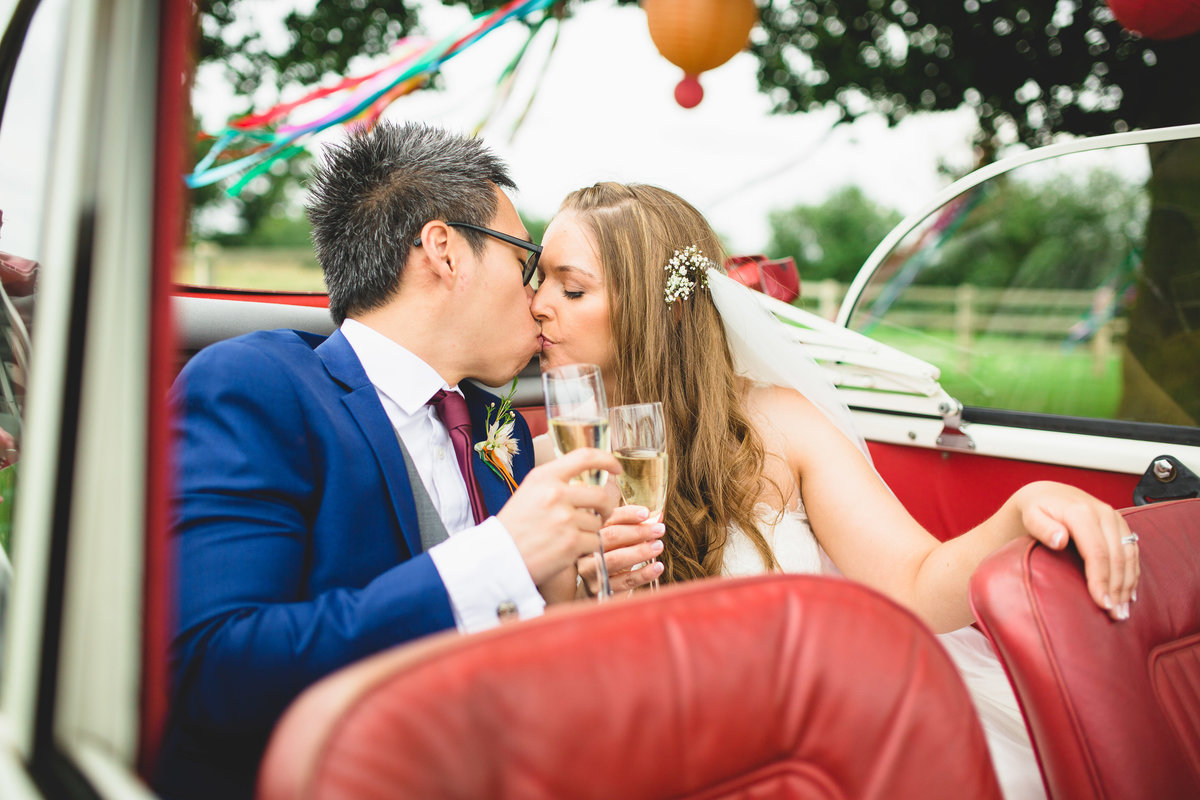 bride and groom in a vintage morris minor wedding car