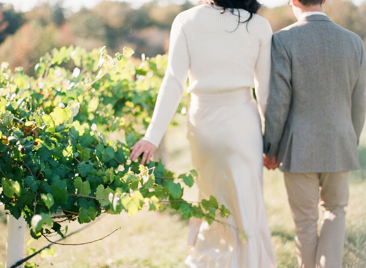 Woman and man walking through vineyards
