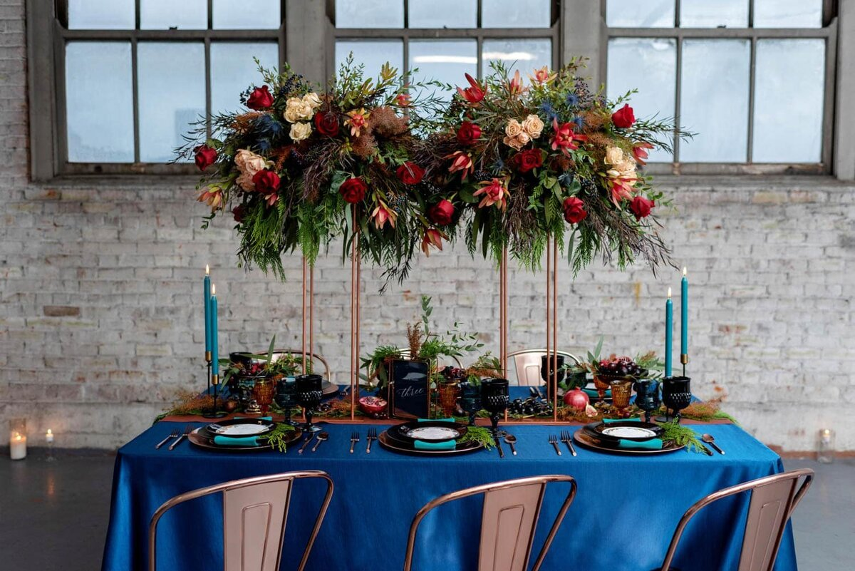 a very pretty flower arrangement is elevated above a reception table by flowers by alana