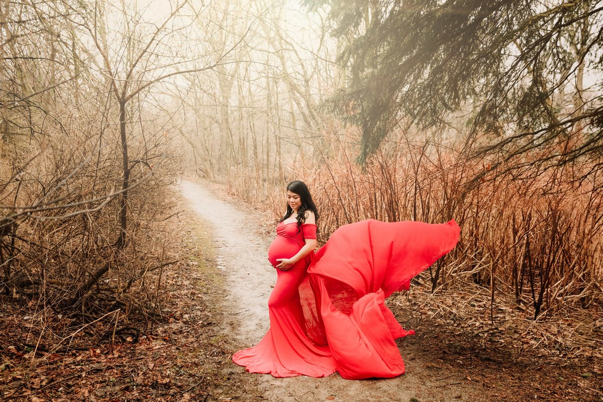 Mom in red maternity gown in forest