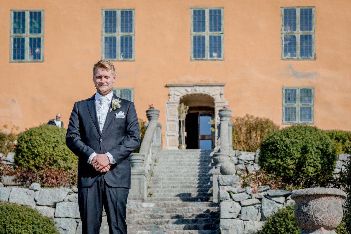 Groom outside the castle standing in the stairs waiting to see his bride for the first time