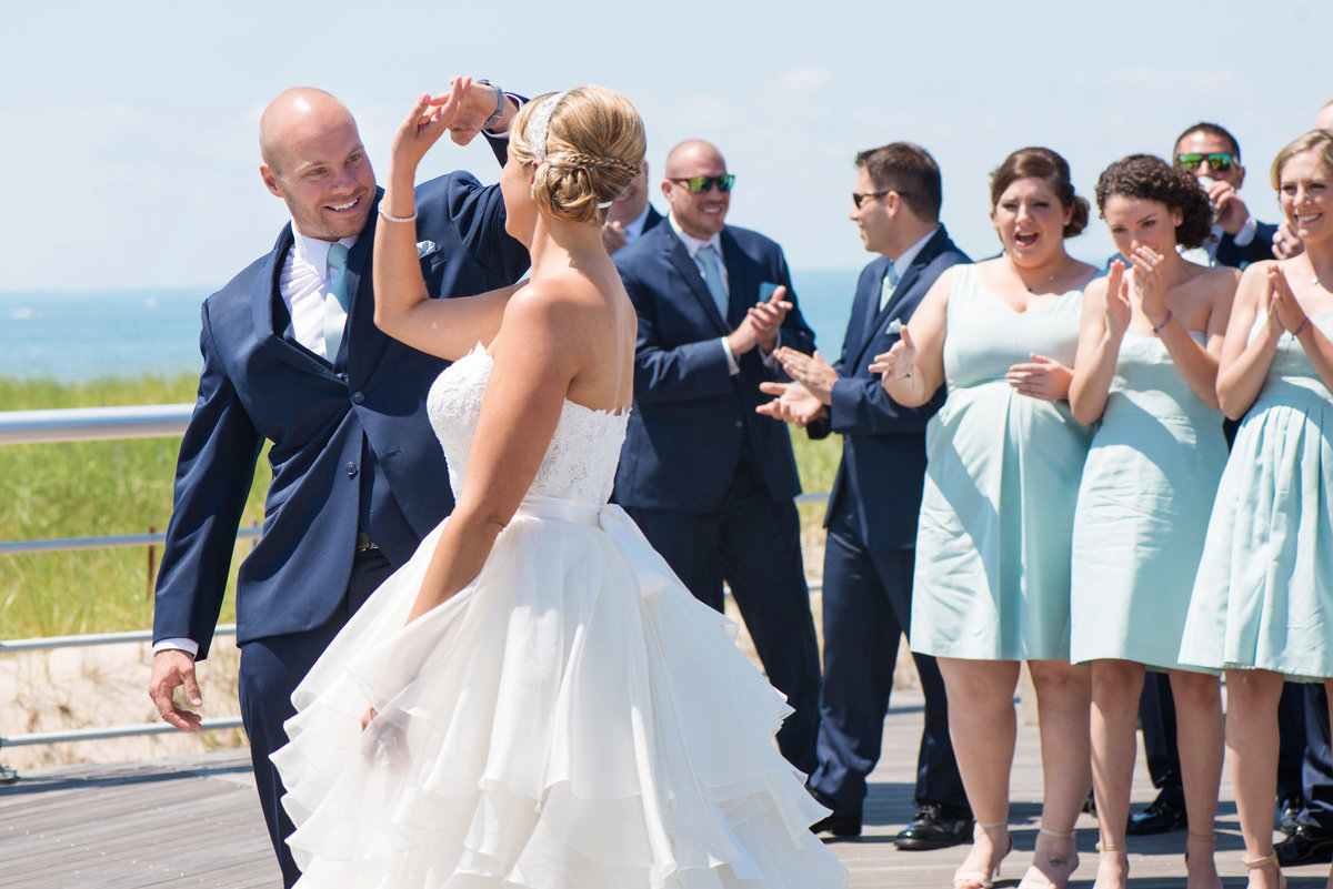 photo of groom twirling his bride on the boardwalk from wedding reception at Pavilion at Sunken Meadow