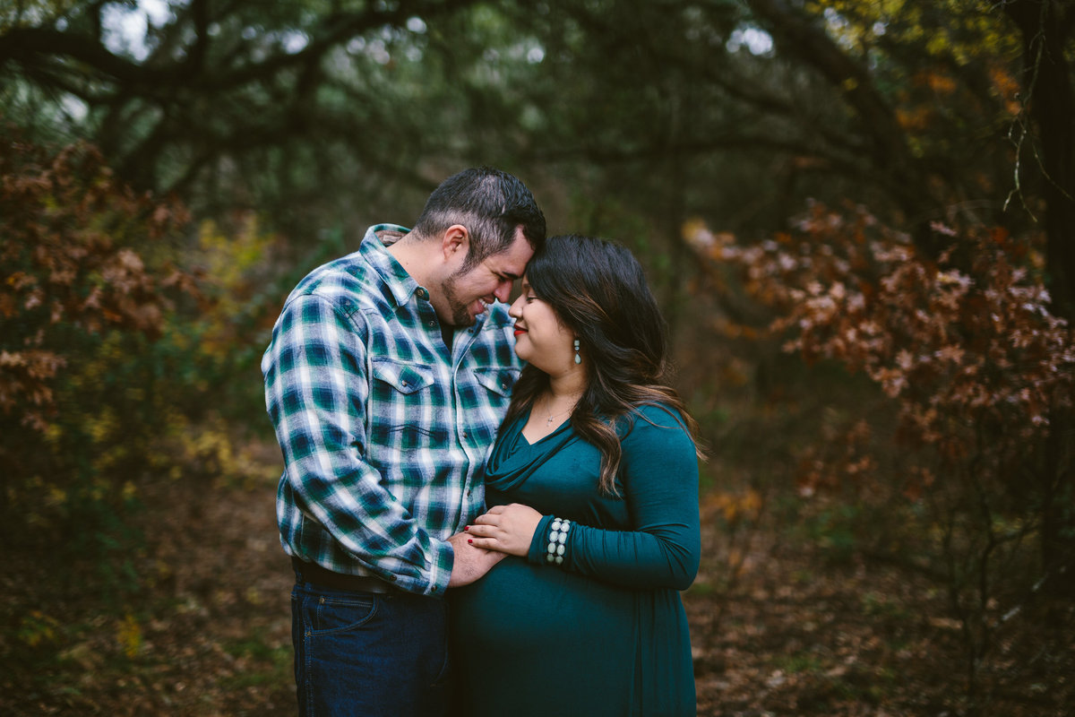 Pregnant couple holding each other for their maternity photography session in San Antonio.