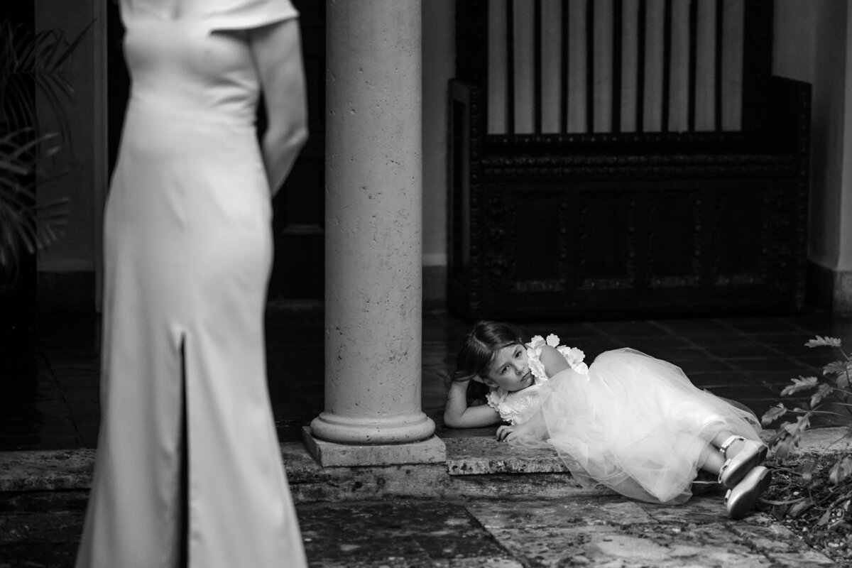 Flower girl lays on floor with a bored look on her face during the first dance in the courtyard of Villa Woodbine