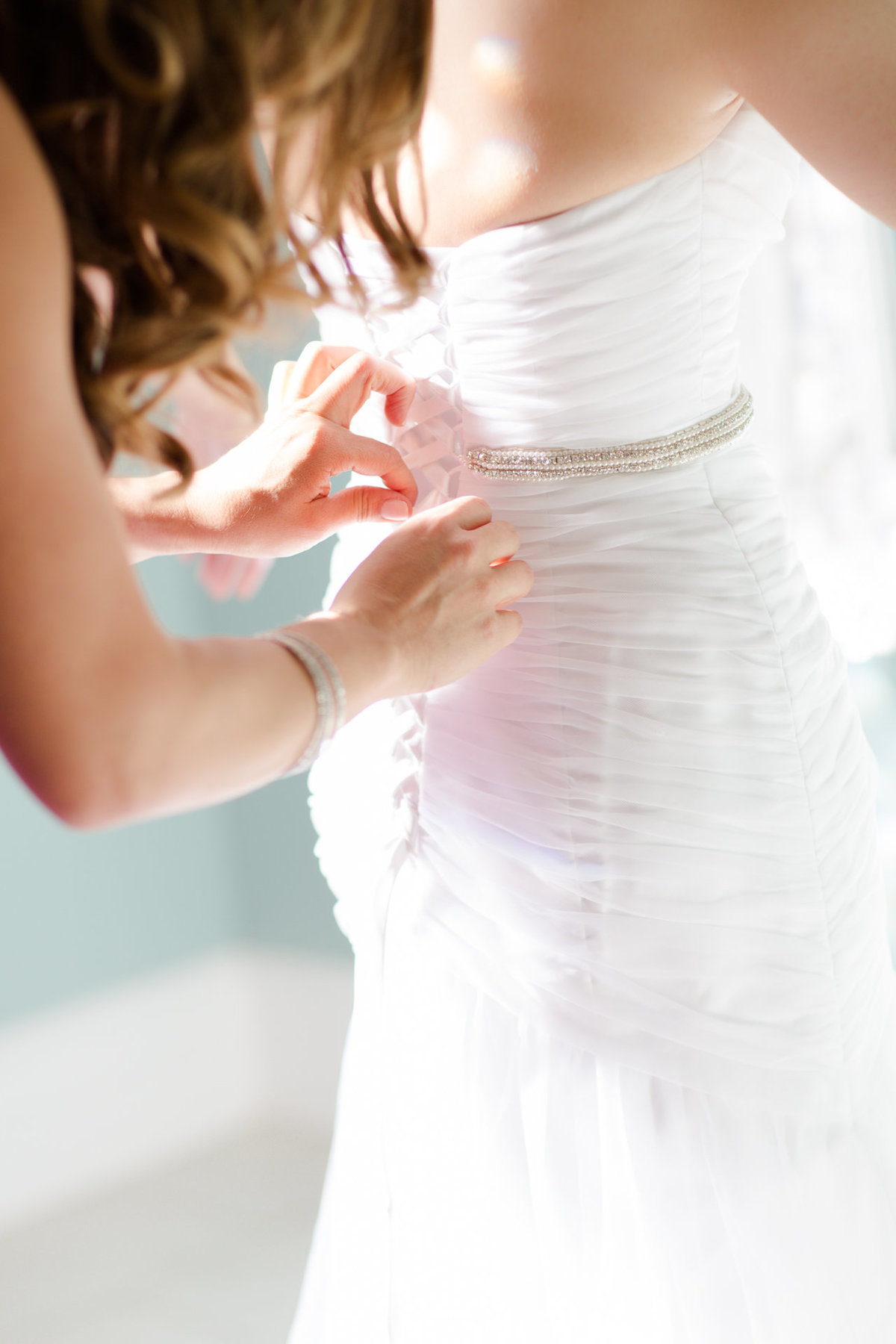 Maid of honor helps bride put on her dress in the bridal suite at villa de amore by matty fran photography