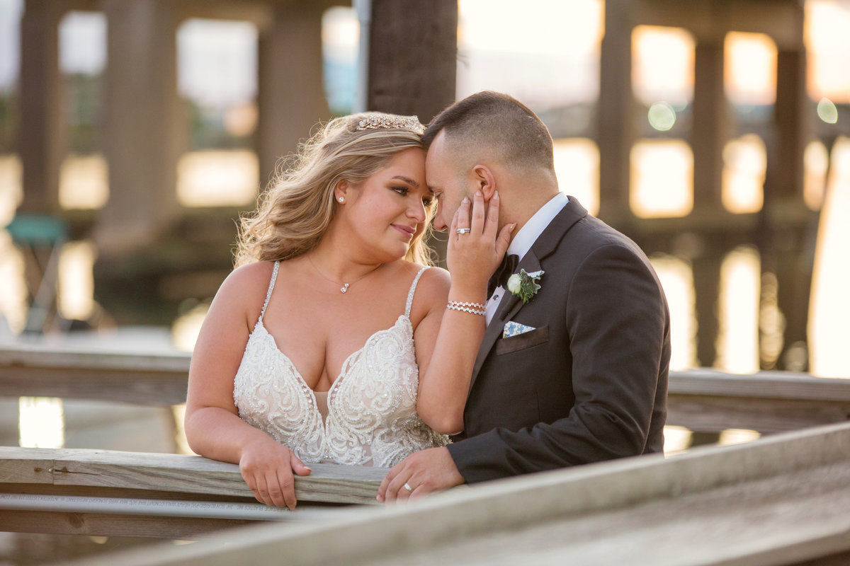 bride holding grooms face on boardwalk of Bridgeview Yacht Club