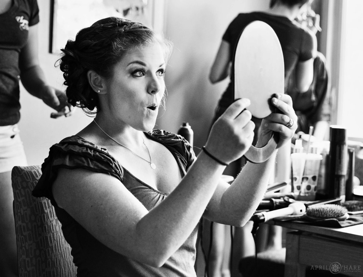 Bridesmaid loves her make up looking in mirror at Wedgewood Mountain View Ranch in Pine CO