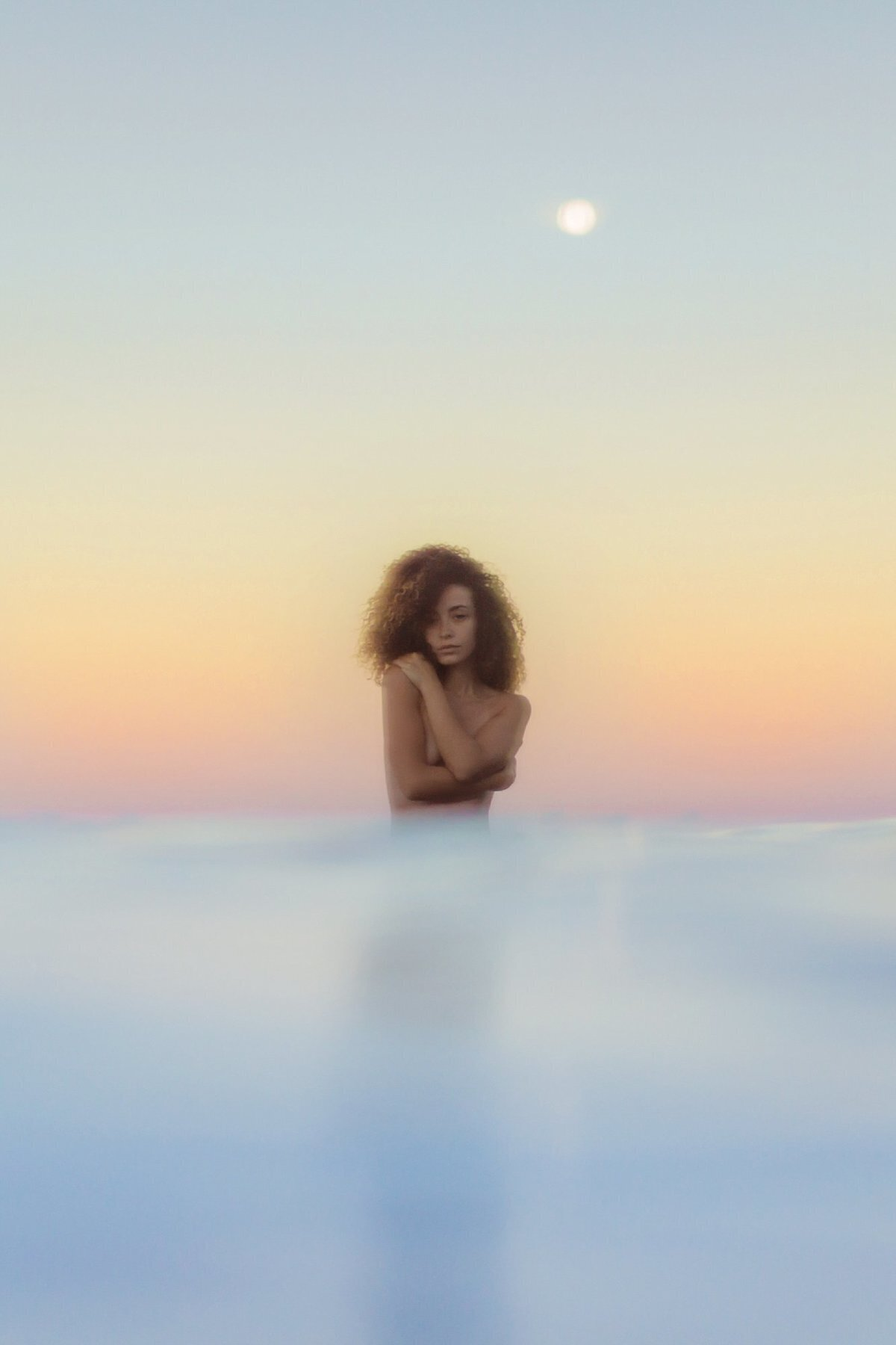 Sunrise pastel tones on Maui with woman holding her chest in the water