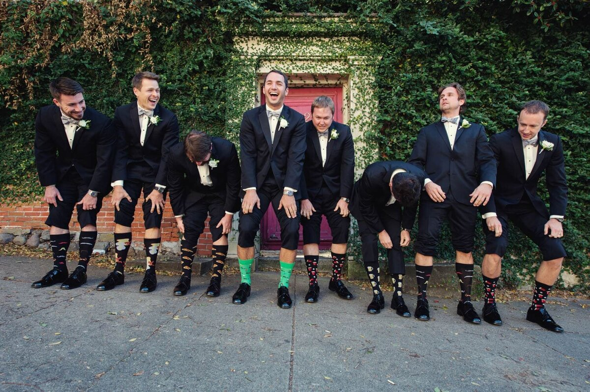 a groom and 7 groomsmen laugh as they  pull up their pant legs to show off their funny socks