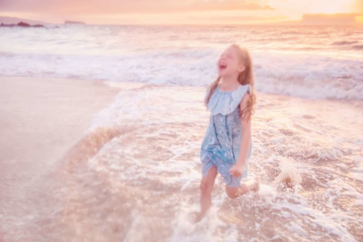 Little girl laughs and runs toward the camera at the beach on Maui