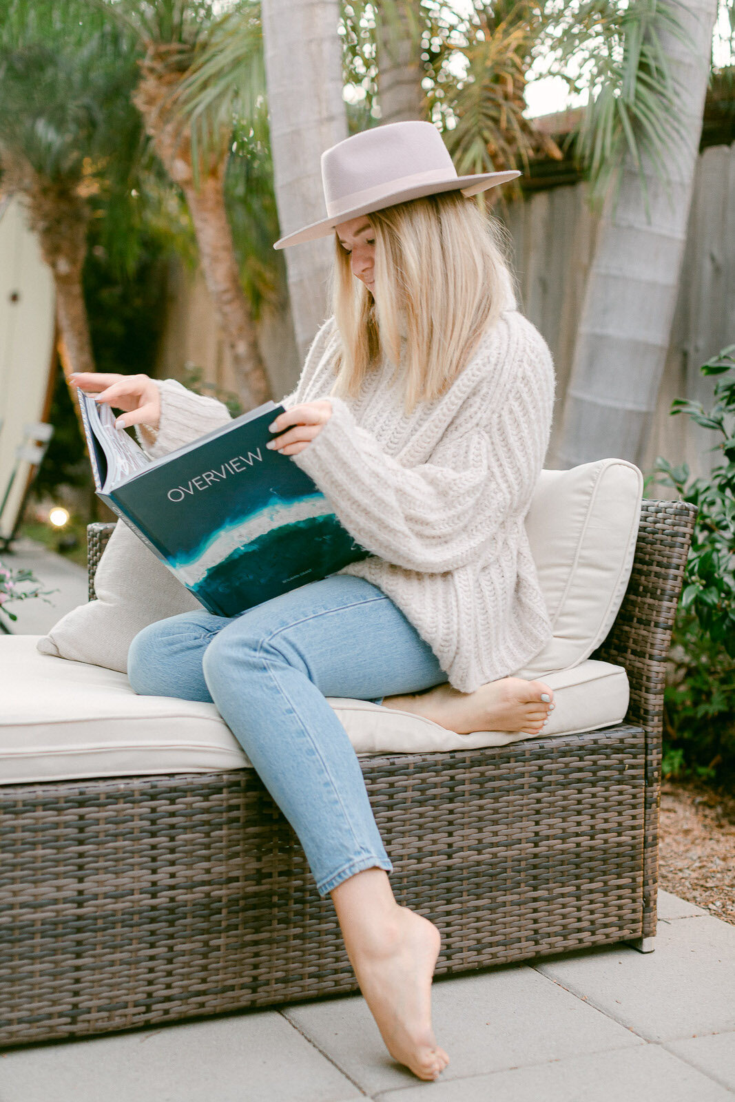 blonde girl reading surfing book on patio