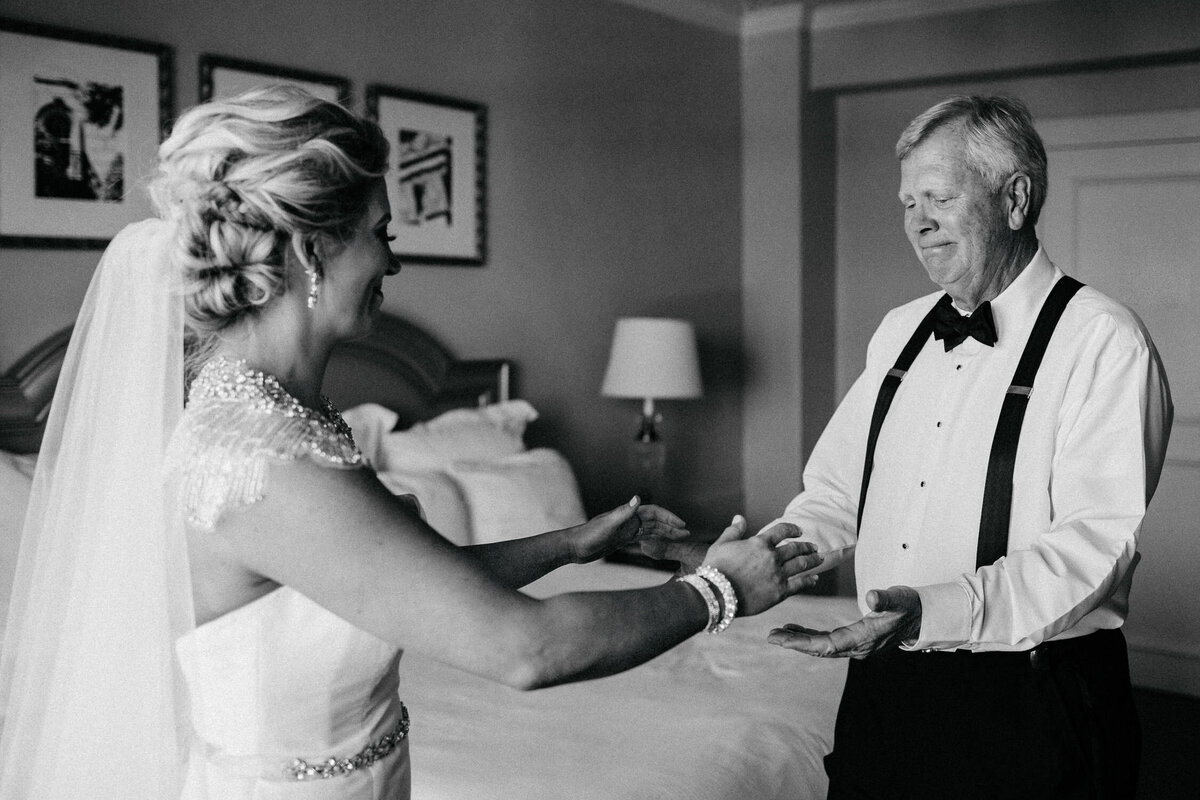 Black and white image of father of the bride seeing daughter in wedding dress for first time